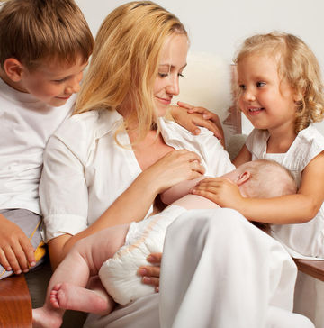 mom breastfeeding with two older children