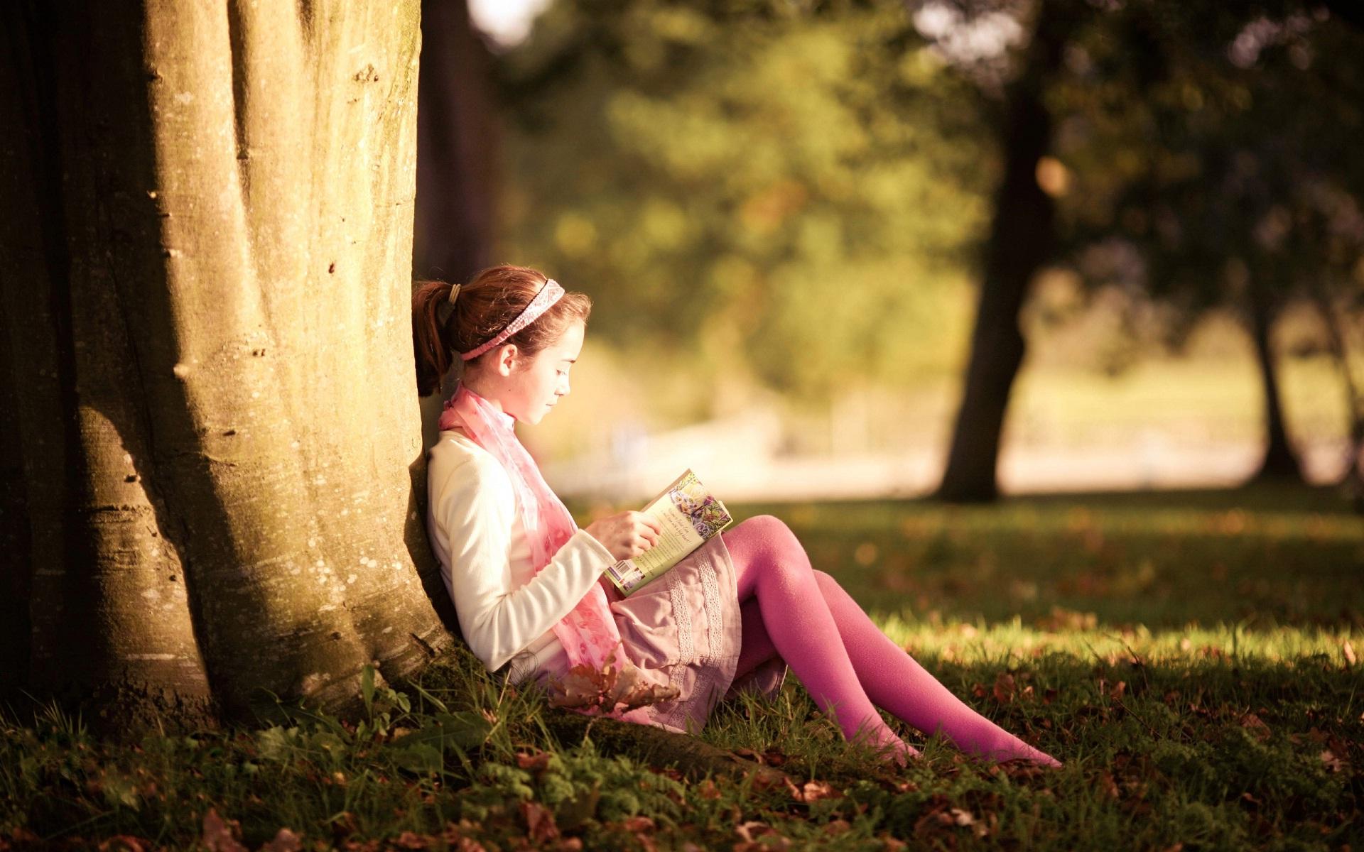 baby reading book in garden